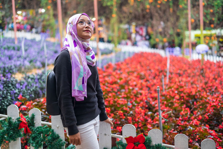 Woman standing on flowering plants