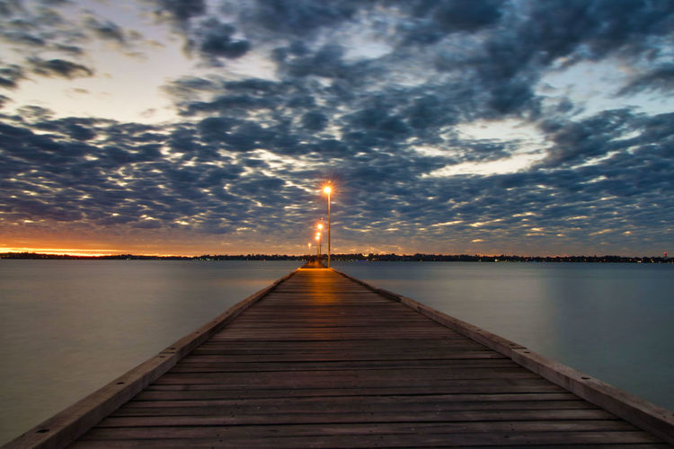Sky Water Sunset Direction Cloud - Sky The Way Forward Tranquility Lake Wood - Material Tranquil Scene Beauty In Nature Scenics - Nature Pier Nature Diminishing Perspective No People Reflection Jetty Idyllic Outdoors Sun Wood Paneling Long