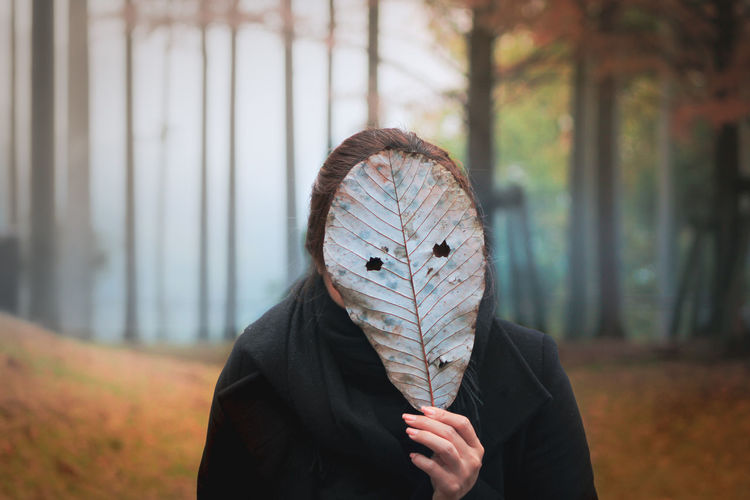 Portrait of person holding autumn leaf outdoors