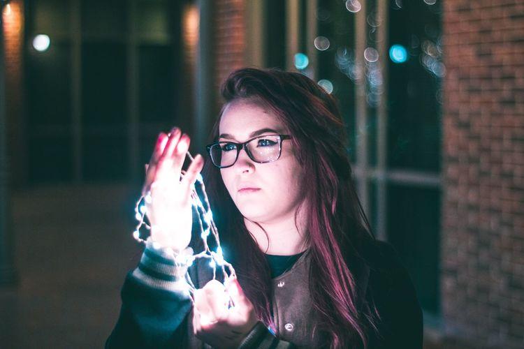 Young woman holding camera at night