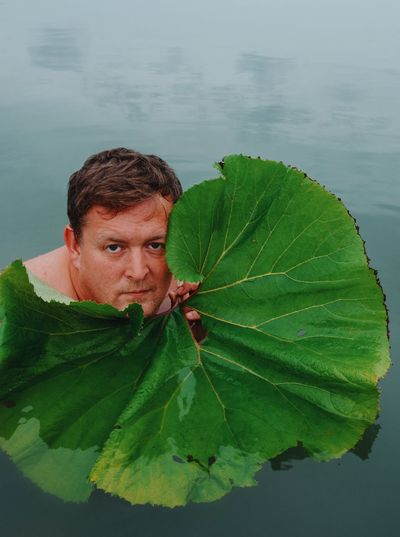 Portrait of man with leaves outdoors