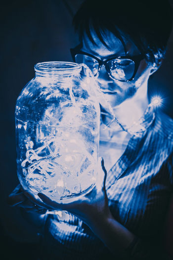 Reflection of man drinking glass