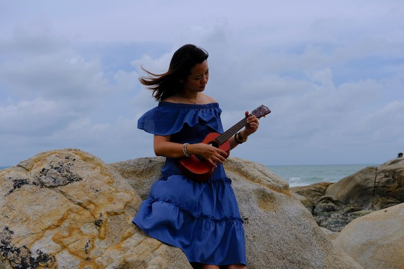 Woman playing guitar while standing by rock at beach