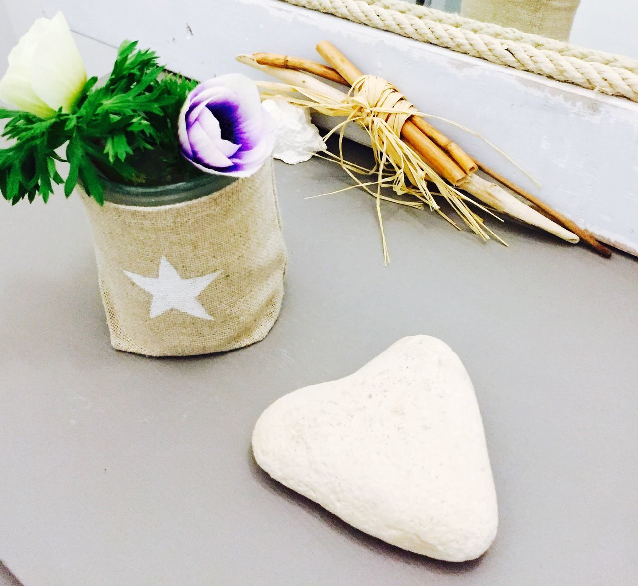 Close-Up Of Pebble With Flower On Table