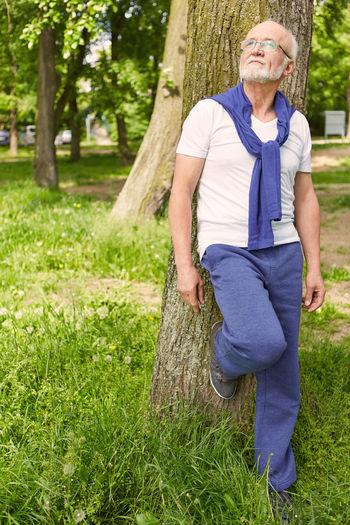 Senior Man Leaning On Tree Trunk At Park