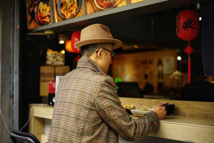 Rear view of boy wearing hat eating food at cafe
