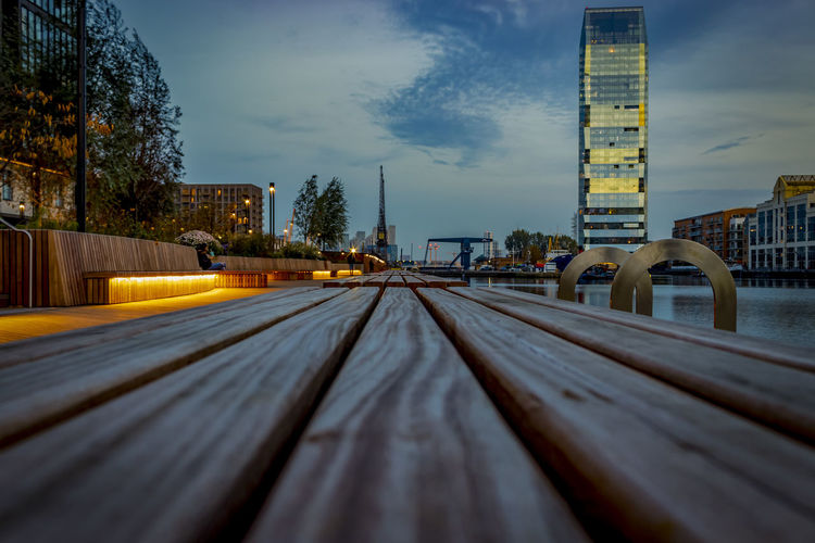 Surface level of bench against sky in city