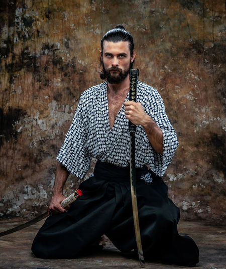 Portrait of samurai with sword kneeling against weathered wall