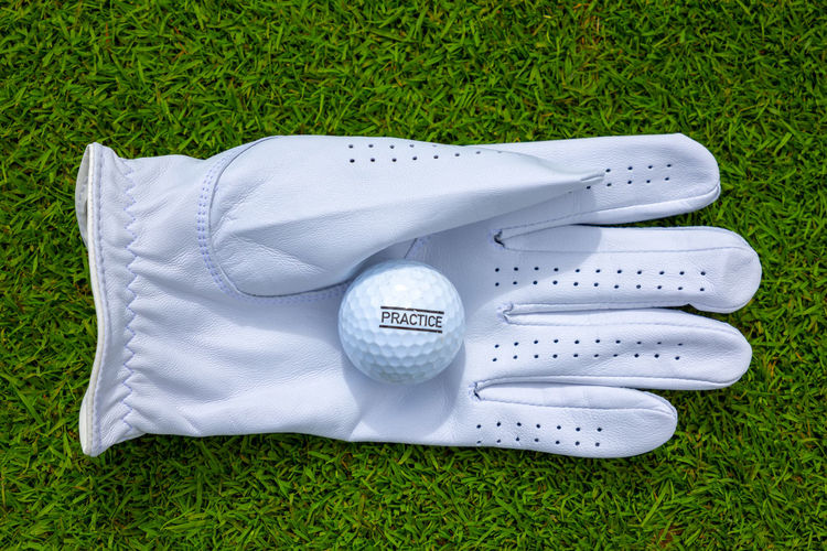 Golf Glove and Practice Ball. Grass Green Color White Color High Angle View No People Directly Above Day Land Sport Absence Outdoors Leisure Activity Golf Two Objects Personal Accessory Sports Equipment New Clean Text Message Practice Simplicity Golf Ball Golf Glove Glove