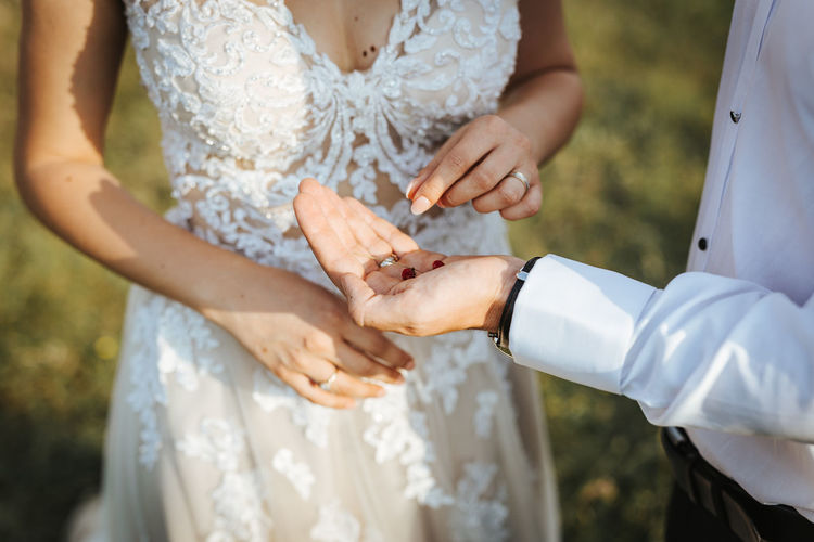 Midsection of bride giving berries on grooms hand