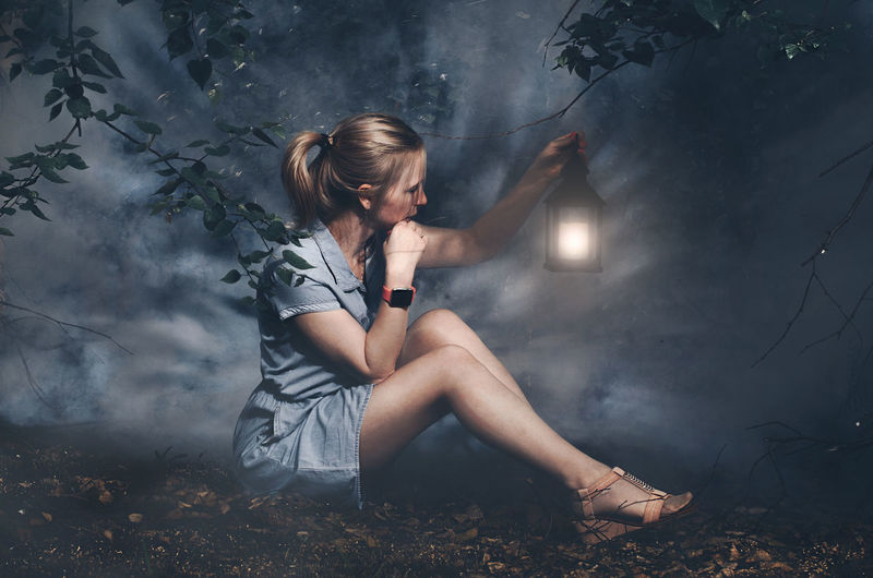 Woman holding illuminated lantern while sitting on land at night