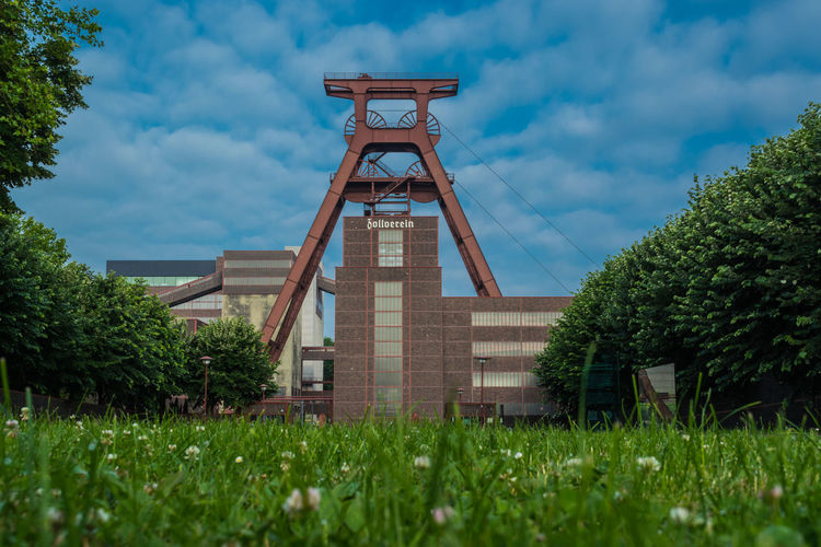 Aufnahme Juli 2013 Mining Industry Weltkulturerbe EyeEm Best Shots Architecture_collection Bergbau Mining Ruhrgebiet Ruhrpott Ruhrpottromantik Zeche Zollverein Architecture Building Exterior Built Structure Cloud - Sky Day Grass Green Color Growth Low Angle View Nature No People Outdoors Sky Tree Wood - Material Mobility In Mega Cities Colour Your Horizn Coal Mine Office Building Mill Stories From The City
