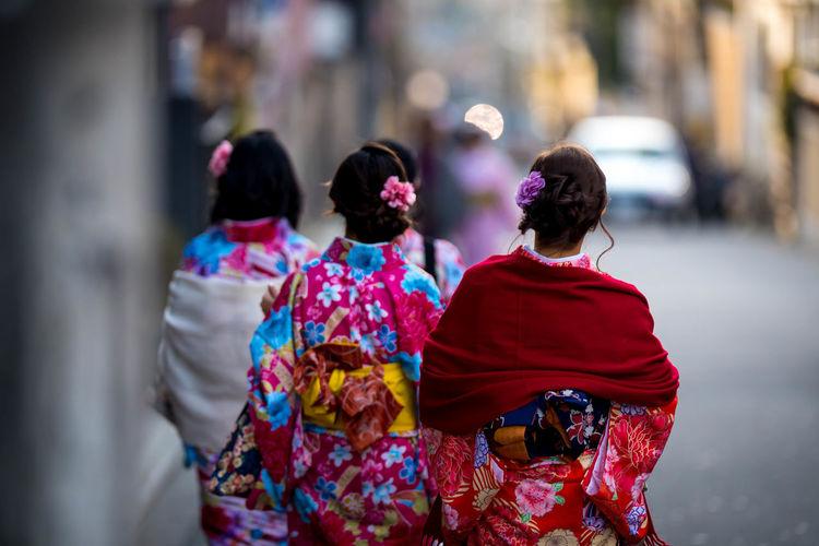 Rear view of women wearing kimono while walking on street in city