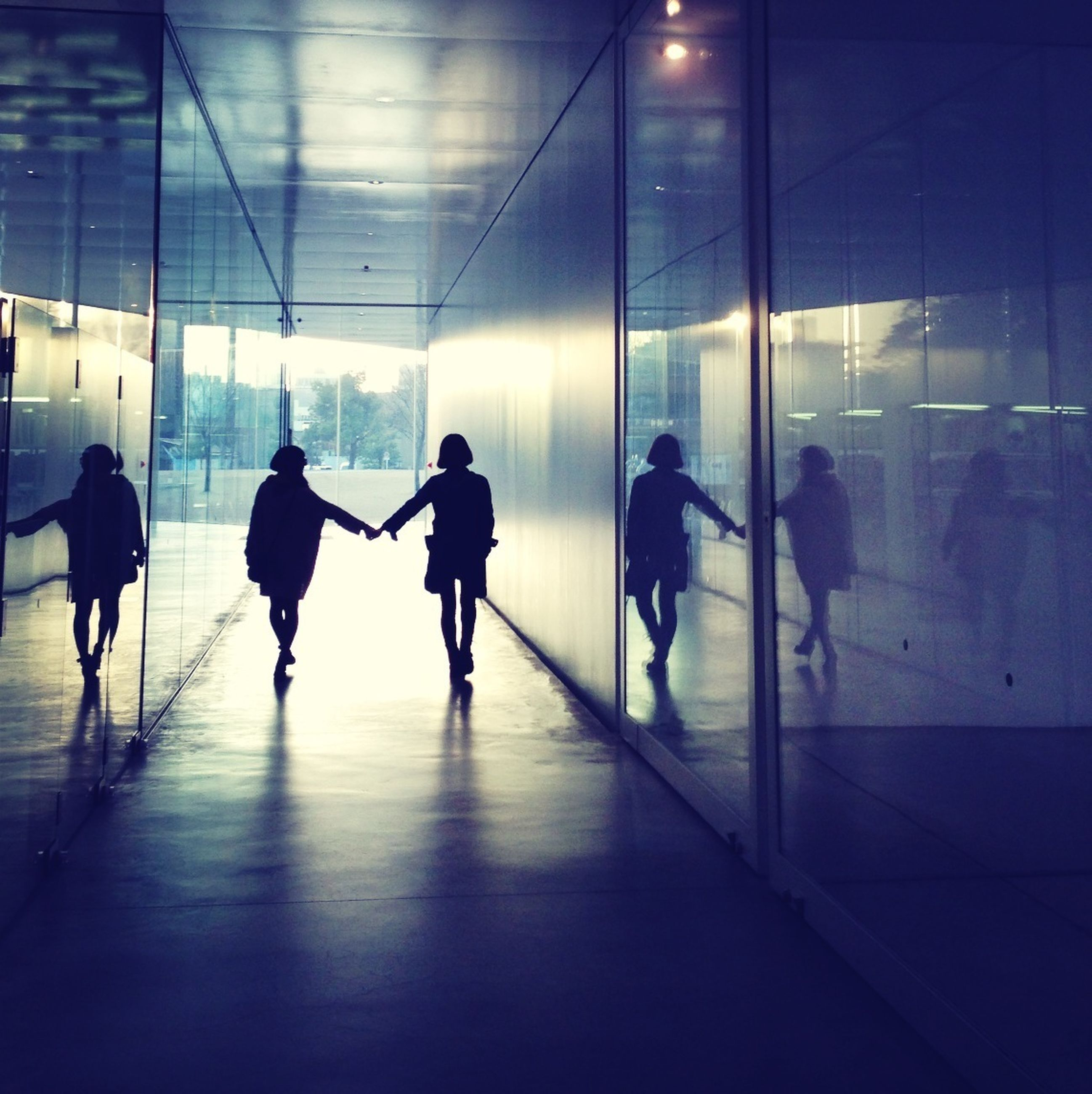 indoors, men, lifestyles, walking, person, silhouette, illuminated, full length, large group of people, flooring, reflection, leisure activity, built structure, airport, architecture, glass - material, medium group of people, city life, corridor