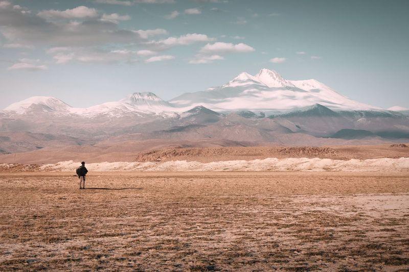 Man standing on desert against mountains