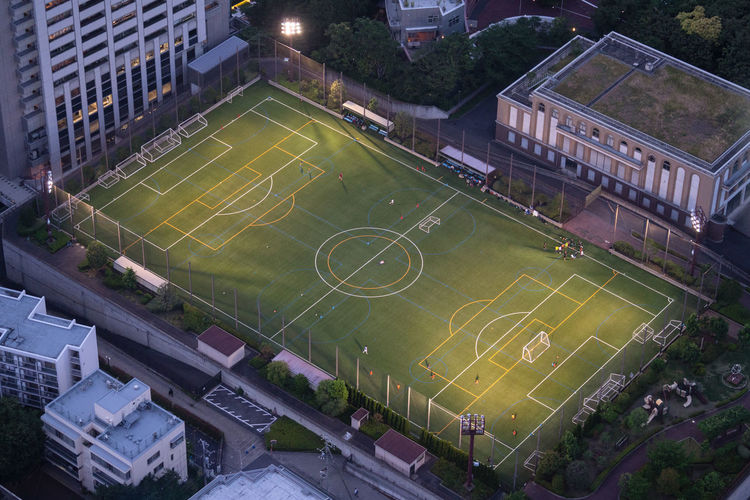 High angle view of soccer field amidst buildings in city