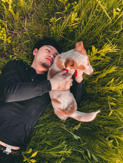Man with dog lying in grass