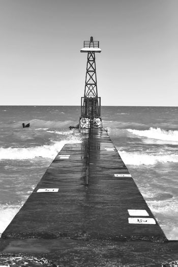 Pier lighthouse on breaker wall in rough waters