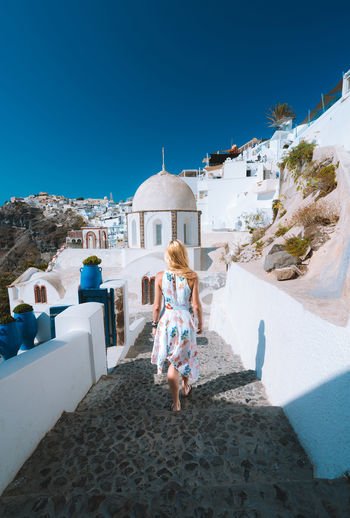 Walking along the beautiful narrow streets of Santorini Check out my print store at http://simonmigaj.com/shop/ and visit my Instagram at http://www.instagram.com/simonmigaj to find out more about me and my work Blonde Center Composition Santorini, Greece Travel Woman Adventure Architecture Blue Building Exterior Built Structure Clear Sky Nature One Person Outdoors Real People Rear View Santorini Sky Travel Travel Destinations Walking