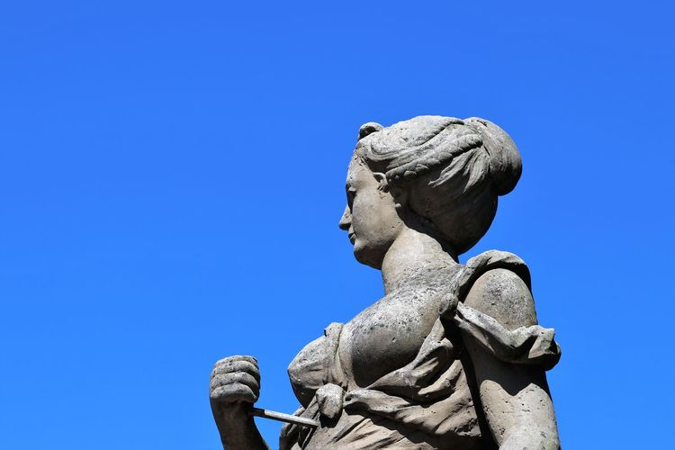 Low Angle View Of Statue Against Clear Blue Sky During Sunny Day