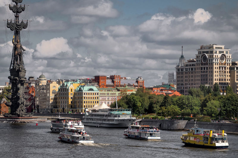 Ferry boats by peter the great statue in moskva river against cloudy sky