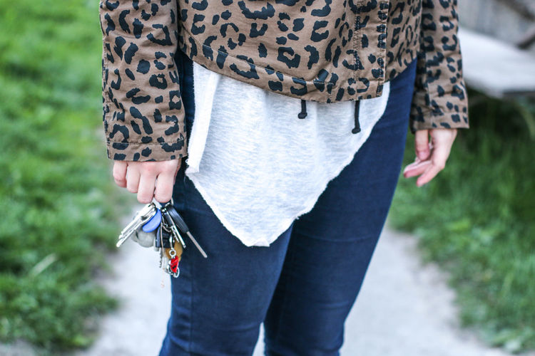 Midsection of woman holding keys while standing outdoors