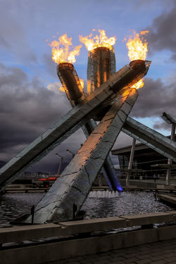 The flames burn bright on the Vancouver Olympic Cauldron, constructed for the 2010 winter Olympics in Vancouver. British Columbia, Canada www.robertdowniephotography.com Love Life, Love Photography 2010 Architecture Bc Built Structure Canada Cauldron City Cloud - Sky Columbia Fire Flame Flames Fountain Ice Lit Night No People Olympic Orange Outdoors Sky Vancouver Water Winter Yellow
