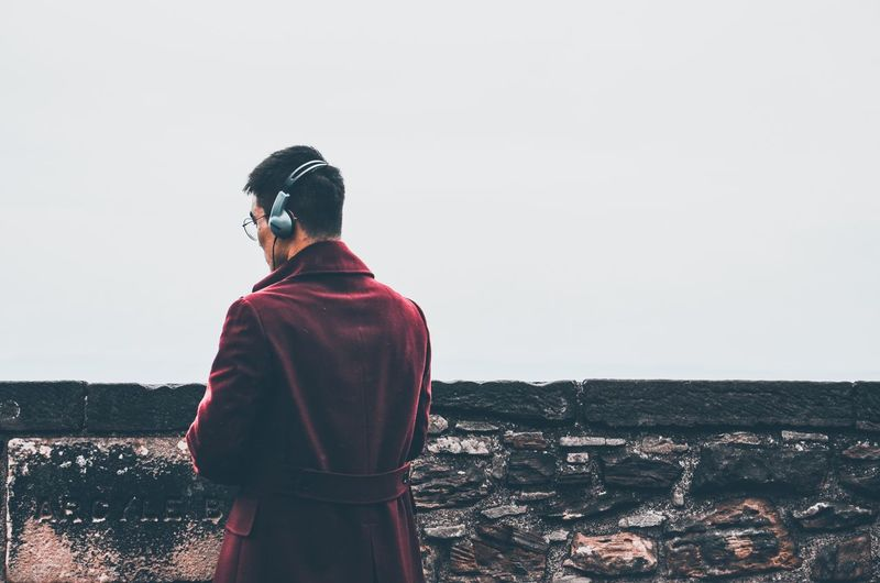 Contemplating Headphones Stone Wall Wall Contemplating Man Red Coat Foggy Sky Real People Rear View Lifestyles One Person Standing Leisure Activity Copy Space Clear Sky Clothing Men Outdoors Casual Clothing Warm Clothing Looking At View