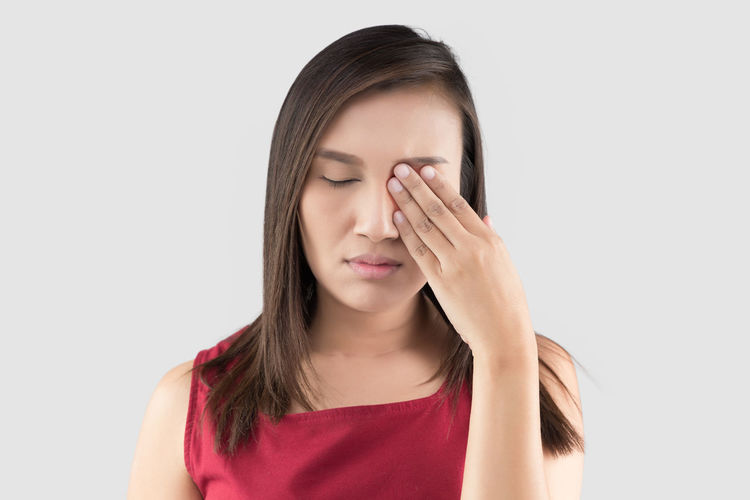 Asian woman in the red shirt has pain in the eye on a gray background, Closing Eyes With Hand, itching, The tired exhausted stressed female suffering from strong eye pai Eye Pain Migraines Itching