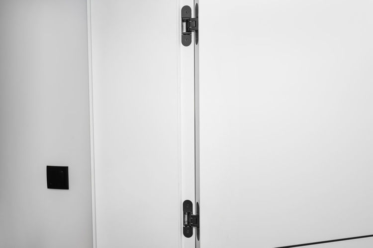 Close-up of door handle on white wall