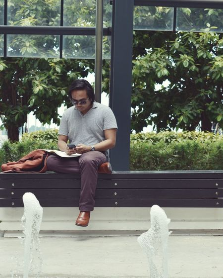 Young man sitting using phone while sitting against modern glass building