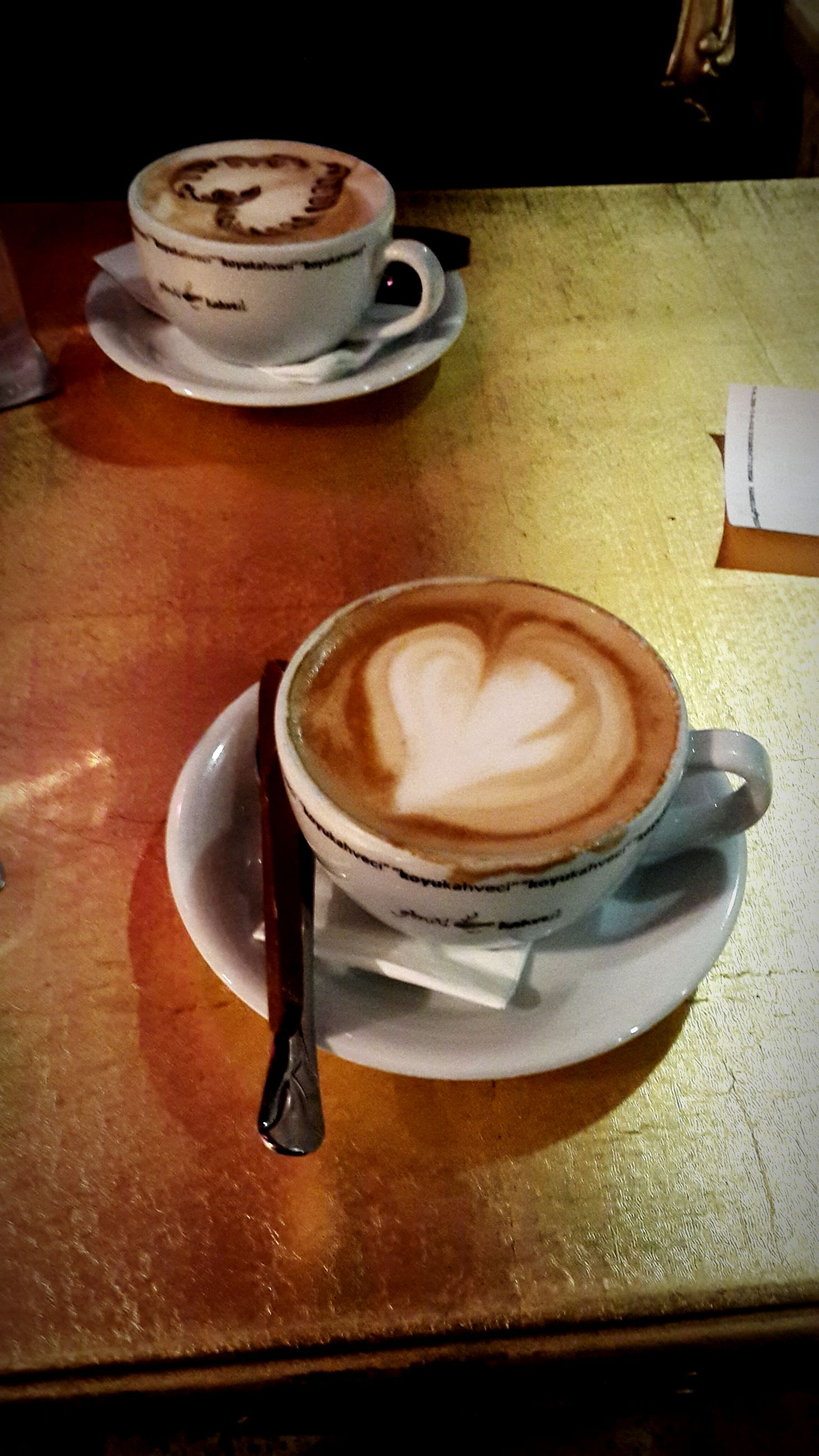 drink, food and drink, coffee cup, refreshment, coffee - drink, saucer, table, indoors, frothy drink, freshness, coffee, cappuccino, still life, cup, spoon, froth art, close-up, beverage, latte, high angle view