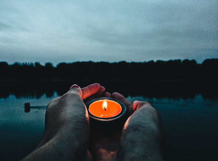 Man with candle by lake against sky