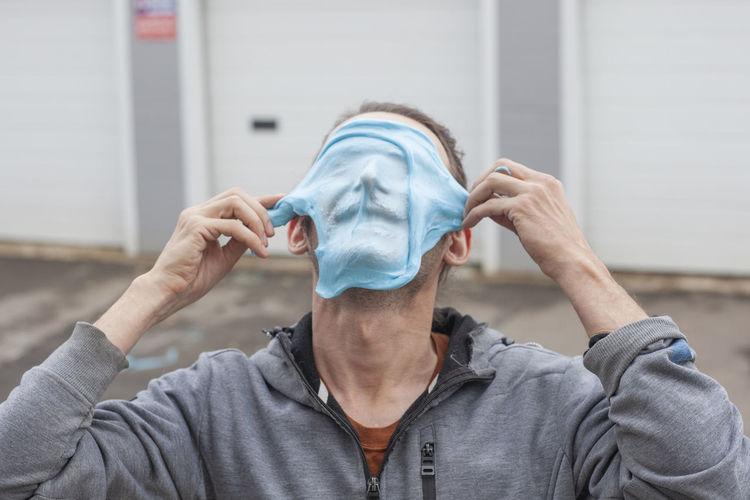 Close-up of man putting mask on face outdoors