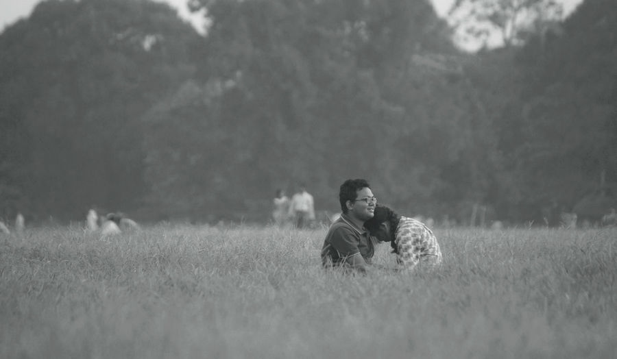 Woman sitting on field against sky