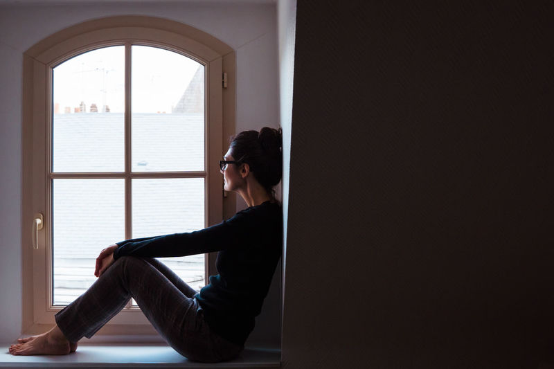 Side view of woman looking through window while sitting by wall
