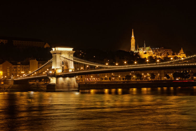 Illuminated chain bridge over river danube against clear sky at night