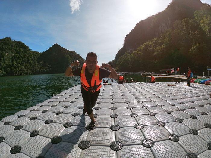 Portrait of man flexing muscles against lake