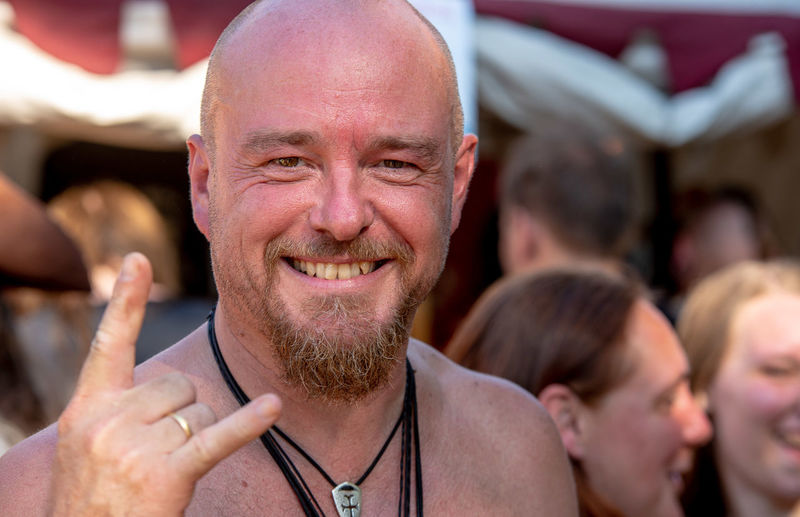 Close-up portrait of shirtless man gesturing horn sign during concert