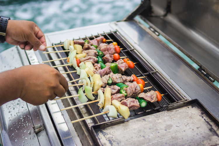 Thailand Barbecue Barbecue Grill Body Part Finger Food Food And Drink Freshness Grill Hand High Angle View Holding Human Body Part Human Hand Meat One Person Outdoors Preparation  Preparing Food Real People Skewer Unrecognizable Person Vegetable Vegetables Wellbeing