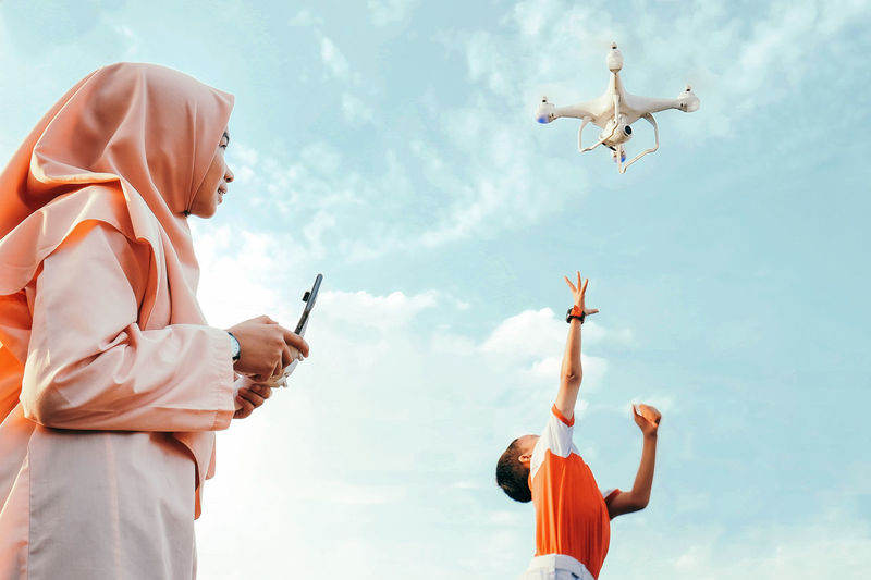 Low Angle View Of Mother Flying Drone While Son Playing With It Against Sky
