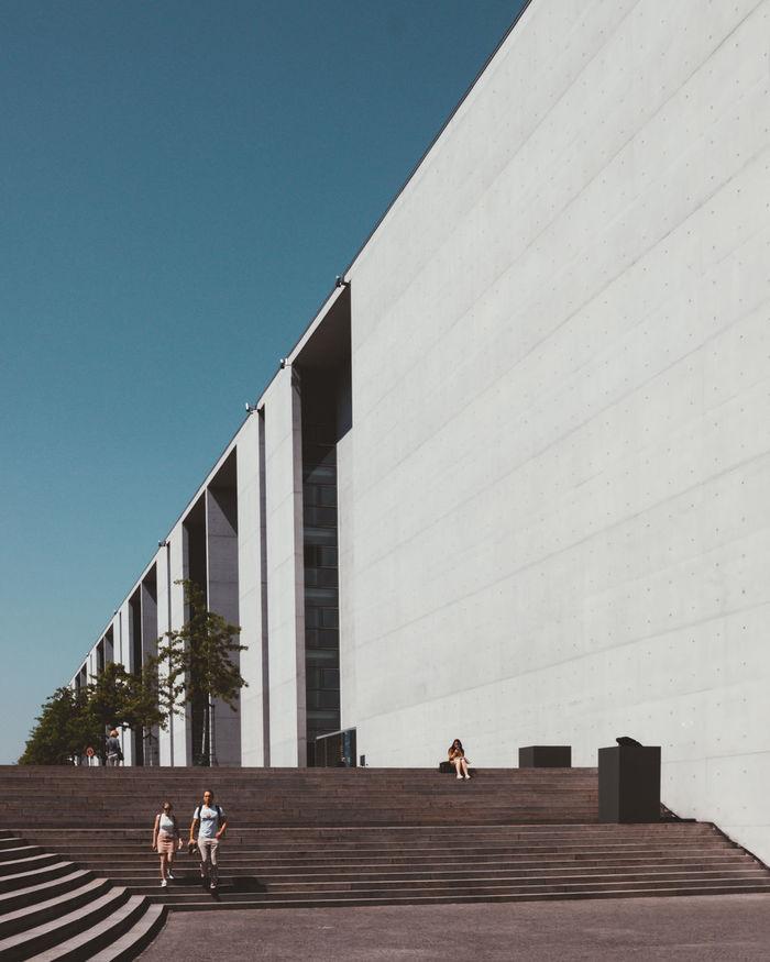 PEOPLE WALKING IN MODERN OFFICE BUILDING AGAINST SKY