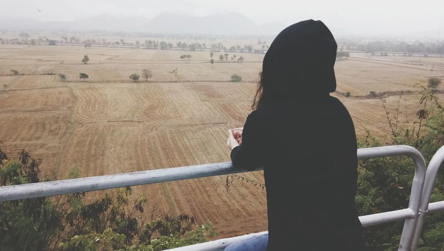 Rear View Of Woman Looking At Field During Foggy Weather