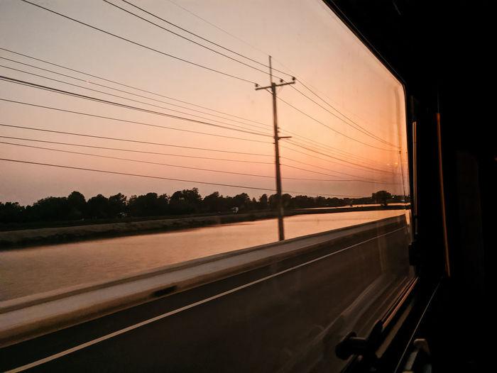 Road against sky seen through car window