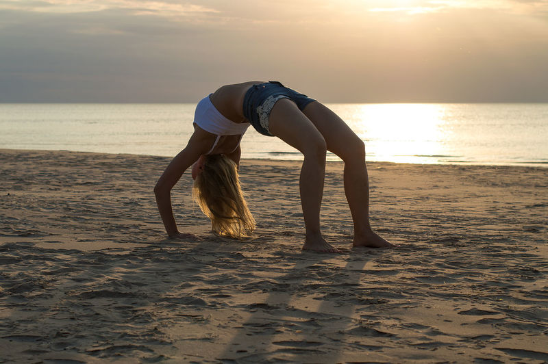 Full length of woman bending over backwards at beach against sky during sunset