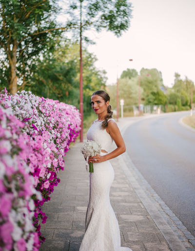 Portrait of bride standing by pink flowers against sky