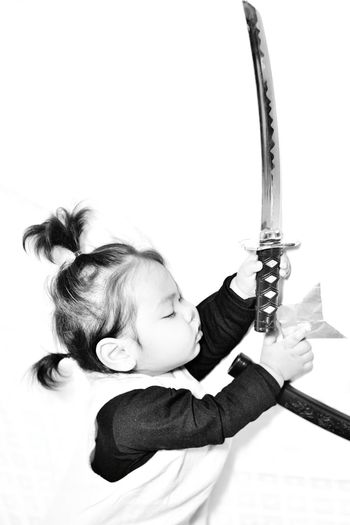 Side view of girl holding katana while standing against wall