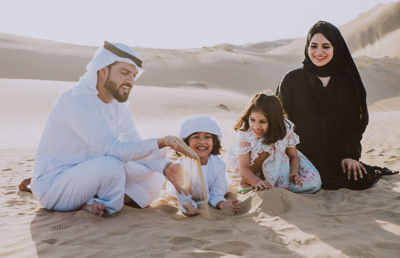 Family playing with sands while sitting at desert