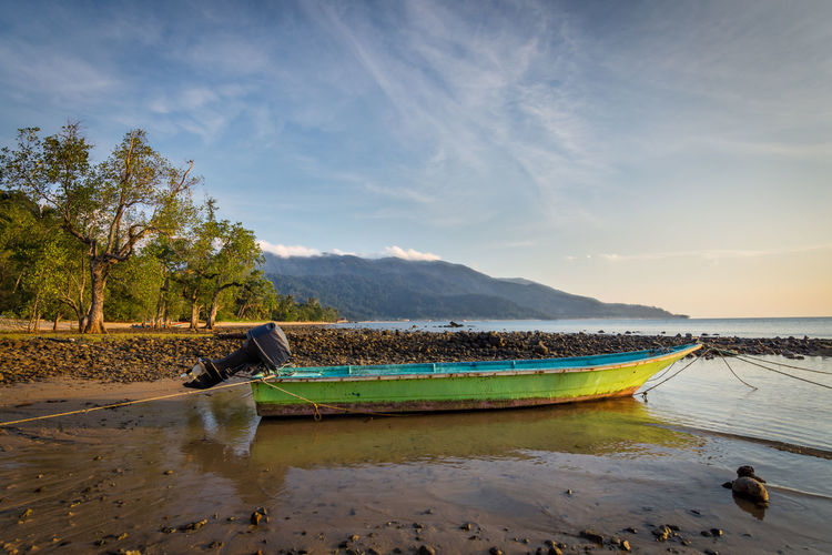 A small green and blue wooden boat with outboard motor sits in shallow water at low tide with trees and hillside in the background. Motor Beauty In Nature Boat Cloud - Sky Day Idyllic Lake Land Low Tide Mountain Nature No People Non-urban Scene Outdoors Plant Reflection Salt Flat Scenics - Nature Sky Tranquil Scene Tranquility Tree Water