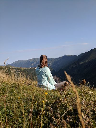 Woman sitting on grass against mountains and sky